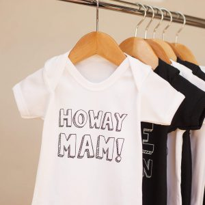 Baby vests with geordie slogans. This one says Howay Mam. It comes in black or white and sizes birth to 18