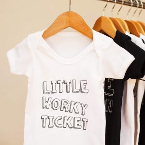 White cotton geordie baby vest with Little worky ticket on the front