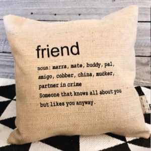 A cushion with the definition of Friend printed on it