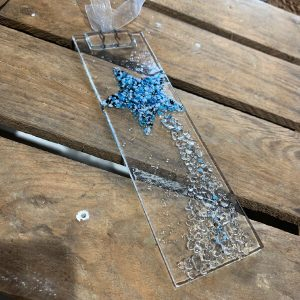 A 22cm piece of hand crafted glass with a hanging fixer so that you can hang it up with ribbon. The glass hanger has a blue and white shooting star design across the glass which will reflect light.