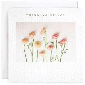 A white square card with a photographic image of some pastel coloured Rannunculus flower and the wording Thinking of you printed above the image