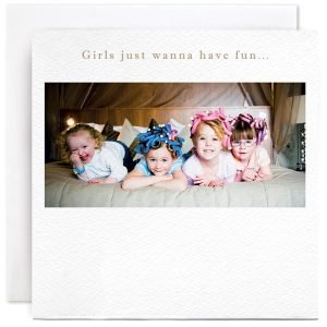 A white square card with a photographic image of 4 little girls having a pamper day with curlers in their hair, lying on a bed.
