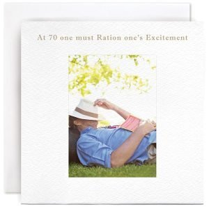 A white square card with a photographic image of a man lying on grass with a hat over his head and a book on his chest. The wording At 70 One Must Ration One's Excitement is printed above the image.