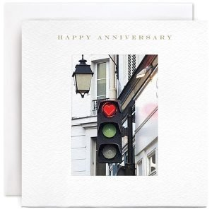 A square card with an image of a set of traffic lights with a lamp above it. The lights are on red and the red light is in the shape of a heart. The words Happy Anniversary are printed above the image.