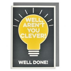 A Well Done card with a bright yellow light bulb design printed on it and the words Well Aren't You Clever embossed and printed in white. The background colour is black.
