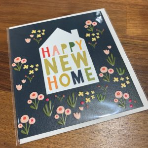 A cream card with dark blue background ad peach and yellow flowers all over it. A white house is embossed and printed in the middle of the card with the words Happy New Home in pastel shades printed inside it. Comes with a white envelope.
