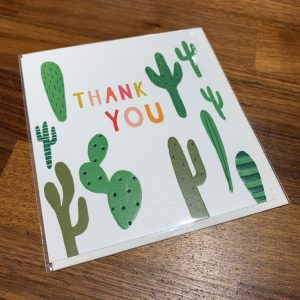 A white card with green cactus all over it and the words Thank You in multi coloured pastel shades of print.