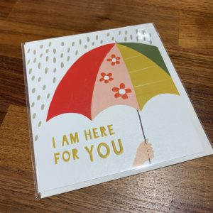 A cream card with an image of a multi coloured umbrella shielding the rain from the words I Am Here For You.