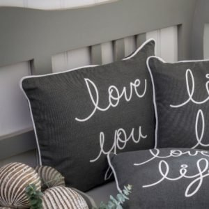 A grey 30 cm x 30 cm cushion with the wording love you printed in white and white piping edges the cushion.