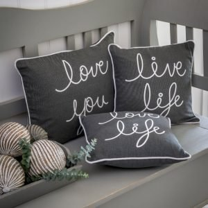 3 cushions on a bench. They are all grey and have wording printed on them in white. The edges of each cushion are piped with a white cord. One cushion says live Life, one says Love Life and the last one says Love you.