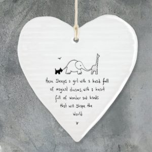 A wobbly cream porcelain heart with the words Here sleeps a girl with a head full of magical dreams, with a heart full of wonder and hands that will shape the world. A lovely gift for a newborn baby girl