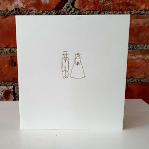 A simple wedding card with a bride and groom printed in gold foil