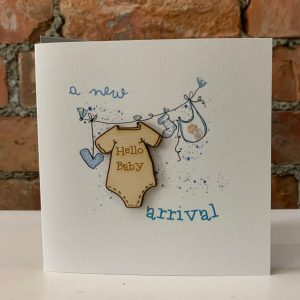 A white square card with a little washing line with baby blue coloured heart bib and socks on it. The words A new Arrival are printed on the card also. A wooden cut out baby vest with the words Hello Baby etched into it is also hanging on the washing line.