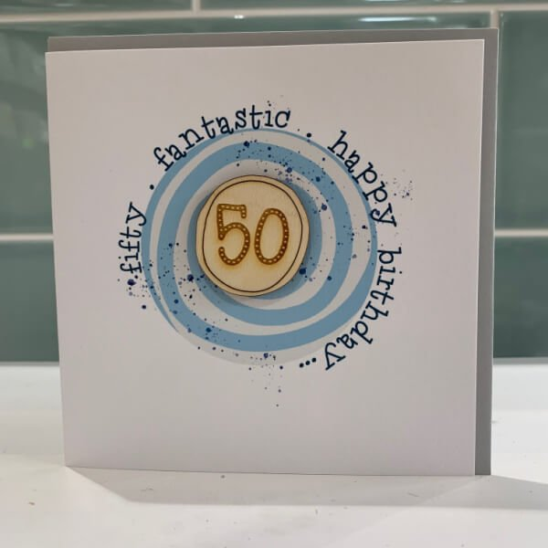 A white square card with a blue coloured swirly circle on it with the words fifty, fantastic and Happy Birthday printed around the circle. In the centre of the circle is a wooden disc with the number 50 etched into it.