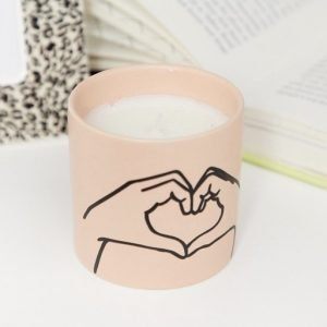 A pink matte ceramic candle with the hand symbol showing love.