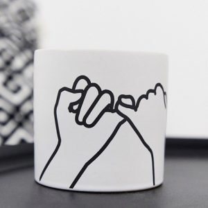 A white matte ceramic candle with an image of hands doing the pinky promise symbol.