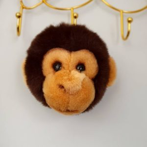 A monkey head soft toy that hangs on the wall of a kids room