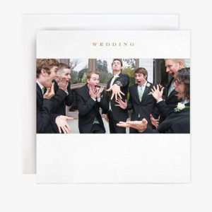 A square card with a photograph of a group of men., One is the groom and he is showing the others his new wedding ring. The others are looking wide mouthed, shocked and excited.