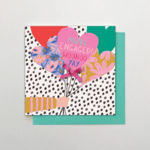 A square card with You're Engaged Woo Hoo Yay on the front and some heart shaped balloons being held out in a bunch. All beautiful bright coloured heart shaped balloons on a black and white spotty background