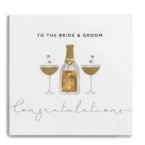 a wedding card for the bride and groom with champagne glasses. decorated with gem stones and gold glitter
