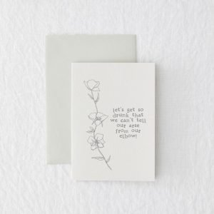 A white card with the wording 'Lets get so drunk that we can't tell our arse from our elbow' printed in grey typewriter font and with a floral image around the wording