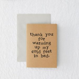 A recycled brown card which is rectangular and has the words 'Thank you for warming up my cold feet in bed' printed in a typewriter style font.