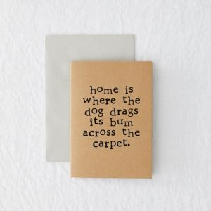 A recycled brown kraft card with the wordin 'Home is where the dog drags its bum across the carpet' printed in black typewriter font.
