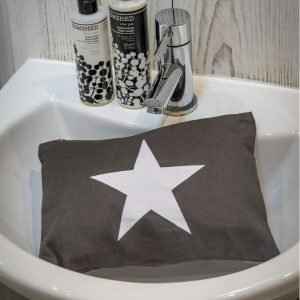 A large dark grey make up pouch with a white star printed on the front of it. The bag is photographed in a bathroom sink.