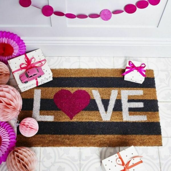 natural coir door mat with navy blue thick stripes and Love printed across the mat.
