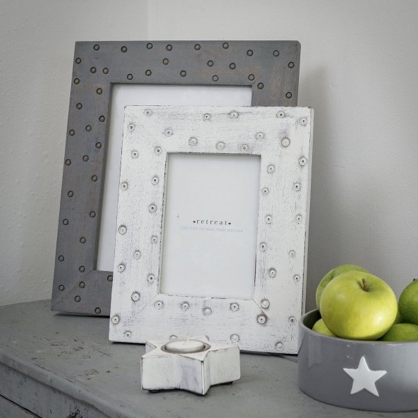 A grey spotty frame with a white spotty frame in front of it.