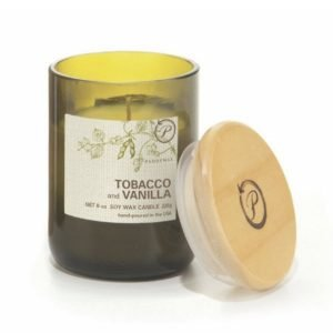 A green jar eco friendly candle with a cream label and the words Tabacco and Vanilla printed on the label. There is a bamboo lid propped next to the candle.