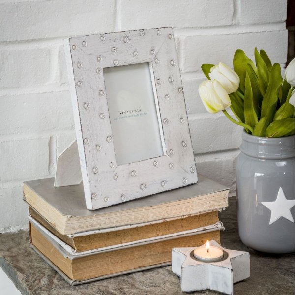 A white rectangular picture frame which has carved spots on it.