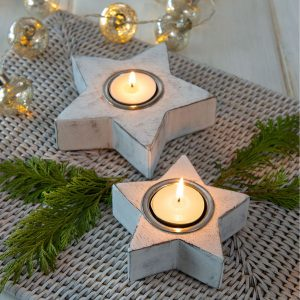 A pair of white star shaped tea light holders.