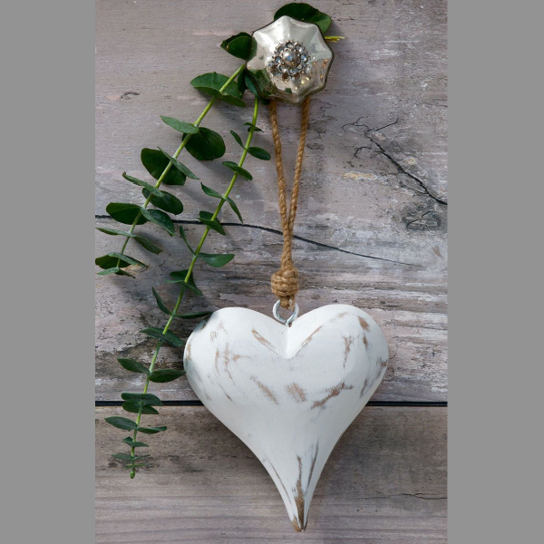 A white washed wooden heart hanging from a knob on a drawer unit.