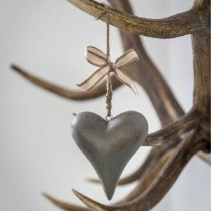 A wooden heart painted with grey distressed finish with string hanger and a cute cream bow hanging from a tree.