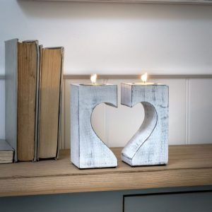A pair of white washed tea light holders that make up a heart shaped decoration.