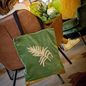 A green plush velvet bag, with a gold strip at the bottom of the bag. It has a gold embroidered fern design and 2 black handles.