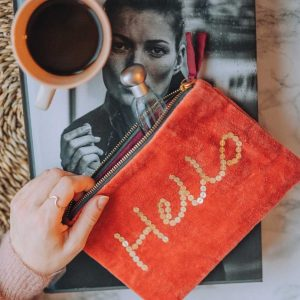 A burnt orange zipable pouch bag with the word Hello made from sewn on gold sequins