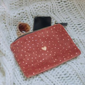 A dark peach make up pouch printed with gold dots and a heart in the centre of it. It has a gold zip at the top of the bag.