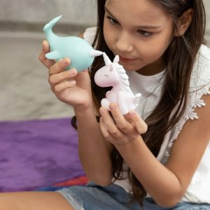 A little girl playing with a lovely unicorn night light and a cute narwhal night light