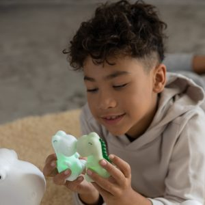 A picture of a little boy playing with a mini LED Dinosaur Night light.