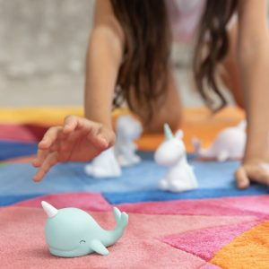 A picture of a little girl playing with a pale blue baby narwhal LED night Light