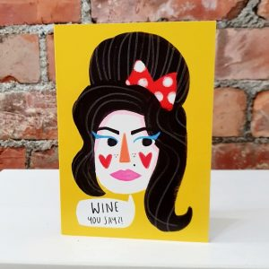 """Wine house amy winehouse greetings card from British illustrator Nichola Cowdery. A classic illustration of Amy on a bright yellow background with a speech bubble """" Wine you says!"""""""