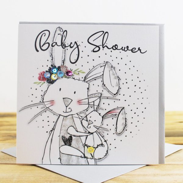 A white square card with an image of two rabbits. A mummy and a baby rabbit. The card is finished with glitter and sequins and the words Baby Shower are printed above the image.
