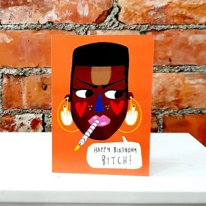"Grace Jones birthday card from British illustrator Nichola Cowdery. An illustration of Grace's face with big earrings, smoking a birthday cake candle on a bright orange background with a speech bubble "" Happy Birthday Bitch"""