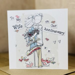 A white square card with an image of a couple cuddling each other There are hearts all around the couple and the wording To My Wife on Our Anniversary are also printed on the card.