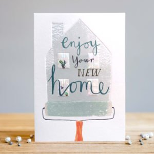 A white rectangular card with an image of a painted house designed with a decorating roller effect and with the wording Enjoy your New Home printed in the centre of it.