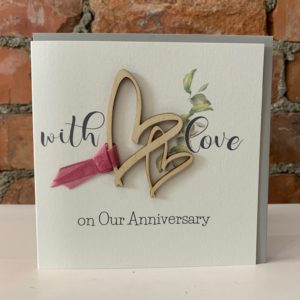 A white card with the words With Love on Our Anniversary printed on it. In the centre of the card are 2 hearts which have been cut out of wood and have a red ribbon attached to them.