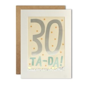 A white rectanuglar card which has a clear cellophane centre with a cream background and the number 30 printed in a foil effect, and the words Ta-Da printed in pale blue. In between the image and the cellophane is glitter and dotty confetti which will move around when it is given a shake. The card comes with a kraft brown envelope.