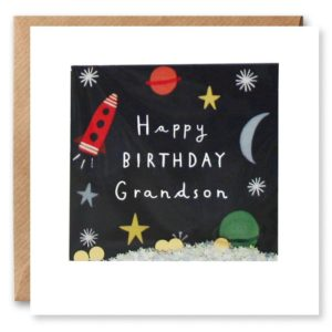 A white square card which has an outer frame which has a cellophane inset infront of an image which has a space theme and a black background. There is a rocket, a moon, planets and stars printed on it. Inside the cellophane is loose glitter and cream do confetti which moves around inside the packet when shaken. The card comes with a square brown craft envelope.